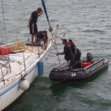 113   Drenched by rain, crew members work to pull the drifting sailboat away