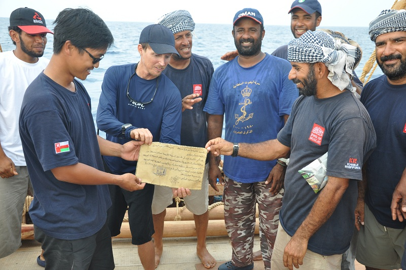 Singaporean crew member Jeff Khoo receives a certificate from Captain Saleh acknowledging Jeff's hard work during the voyage