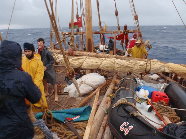 With sails down, the crew waits out the storm