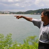 093   Galle citizen Mr. Upasena  points to the place on Davata beach where he was swept away by the tsunami
