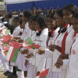 052   Local school children wave Omani flags in welcome.
