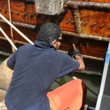 051   Fahad Al Shaibi applies another protective coat of fish oil to the hull in preparation for the final leg to Singapore